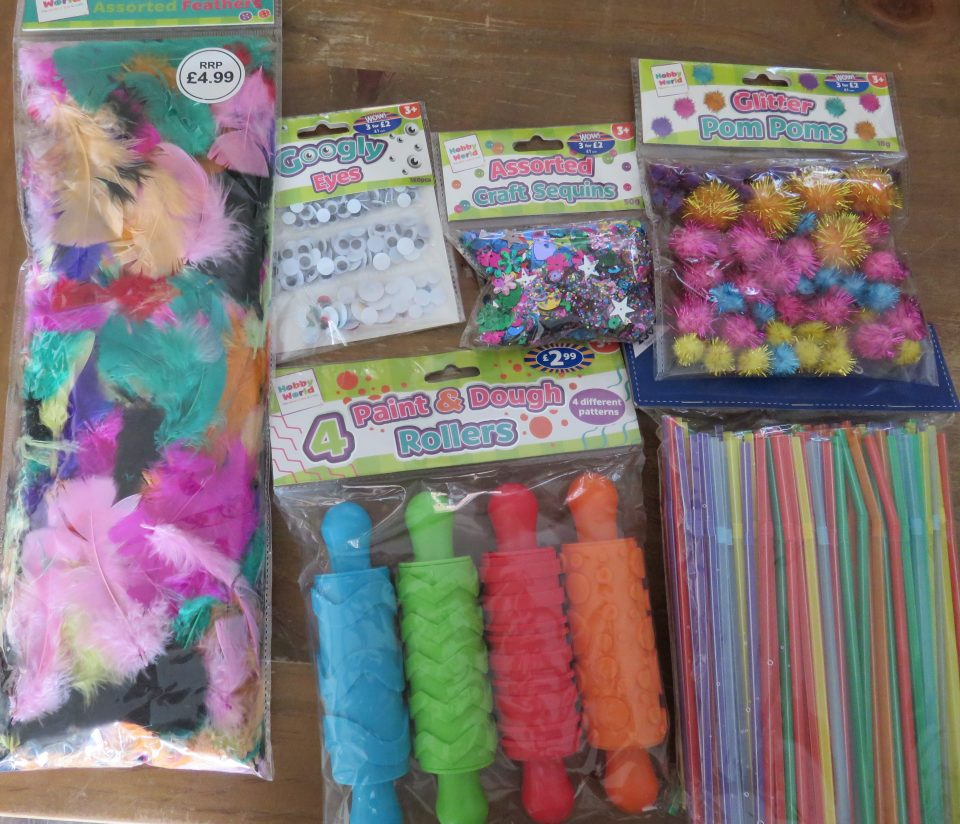 table of crafting goodies including pom poms, stars, goggly eyes, feathers, straws and rolling pins