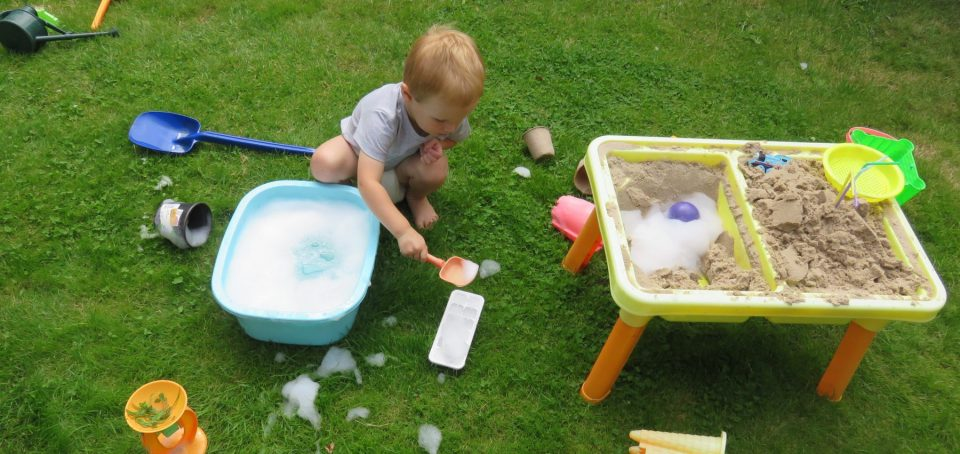child on lawn with a sand and water table plus lots of toys and foamy water in a bowl