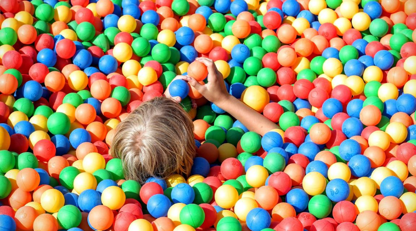child in a ball pit at soft play