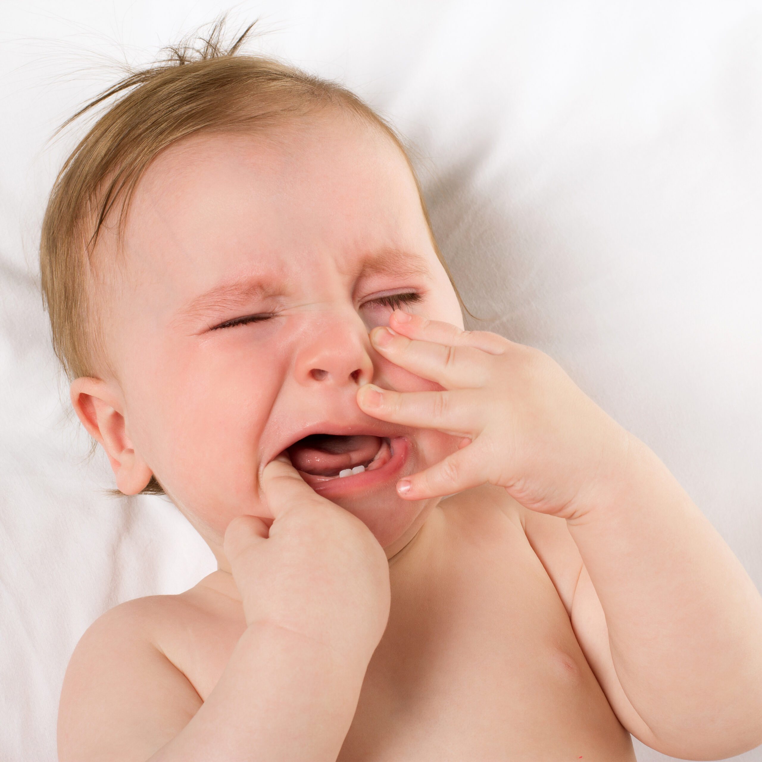 baby crying in pain from teething symptoms