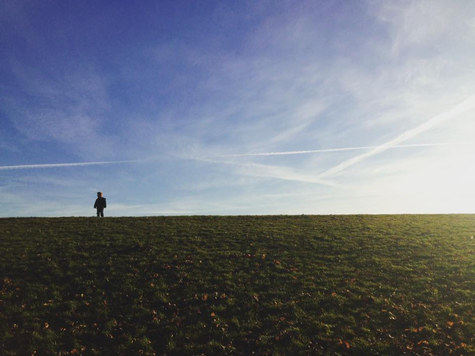 boy stood on top of a hill