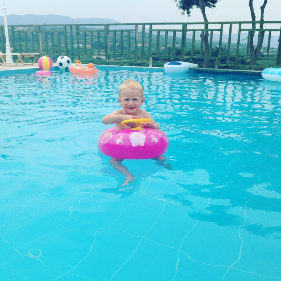 child in a floating car in a pool