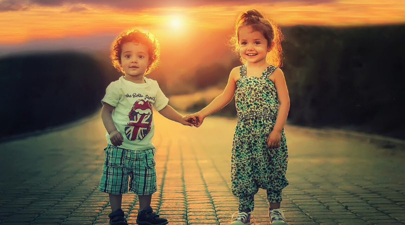 a two year old boy holding hands with a three year old girl at sunset