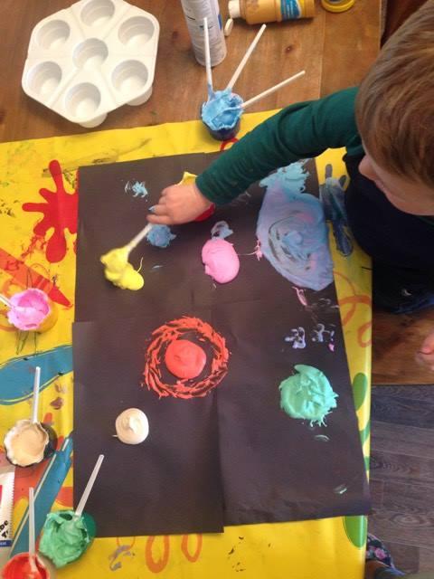 child making foam planets on black paper