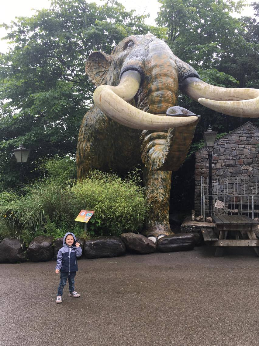 Jake stood by a huge statue of a woolly mammoth