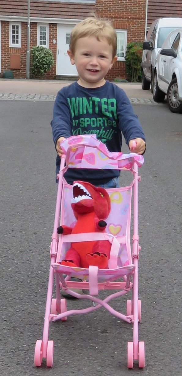 Jake pushing a T rex toy in a pink pushchair