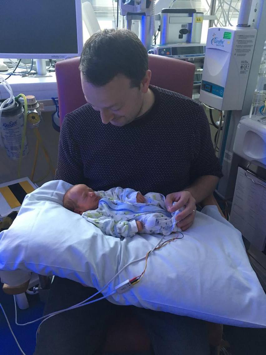 Rob holding William in NICU on a pillow for comfort