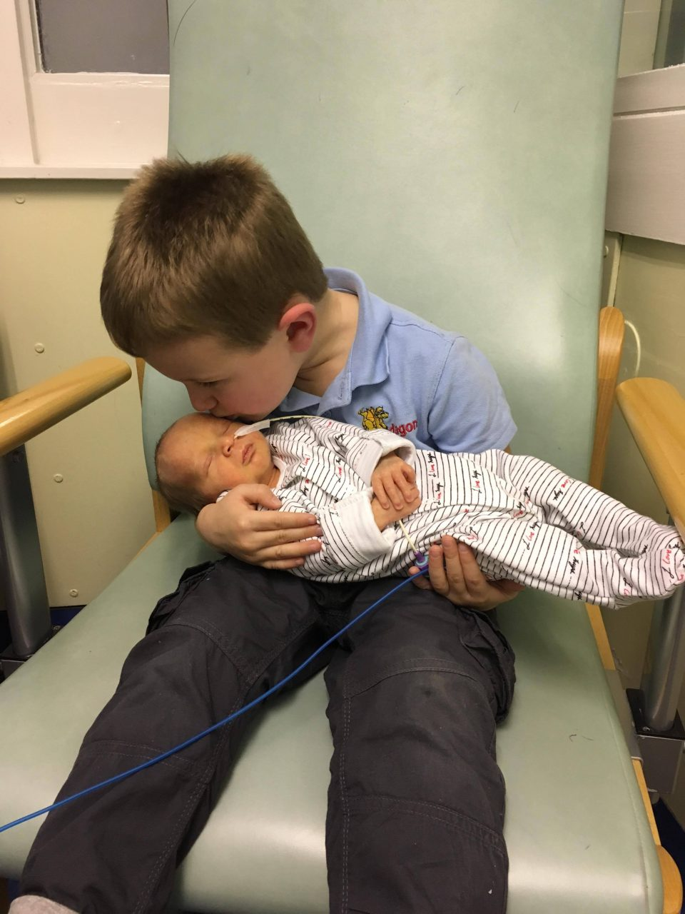 baby with brother being held for the first time and receiving a kiss on the head