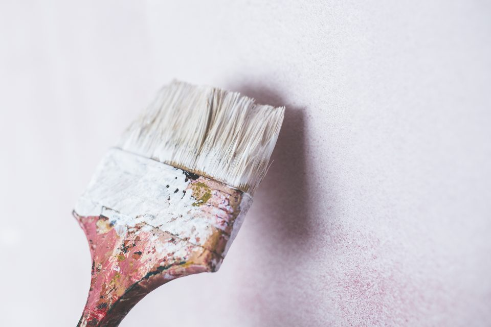 a paintbrush with white paint on it