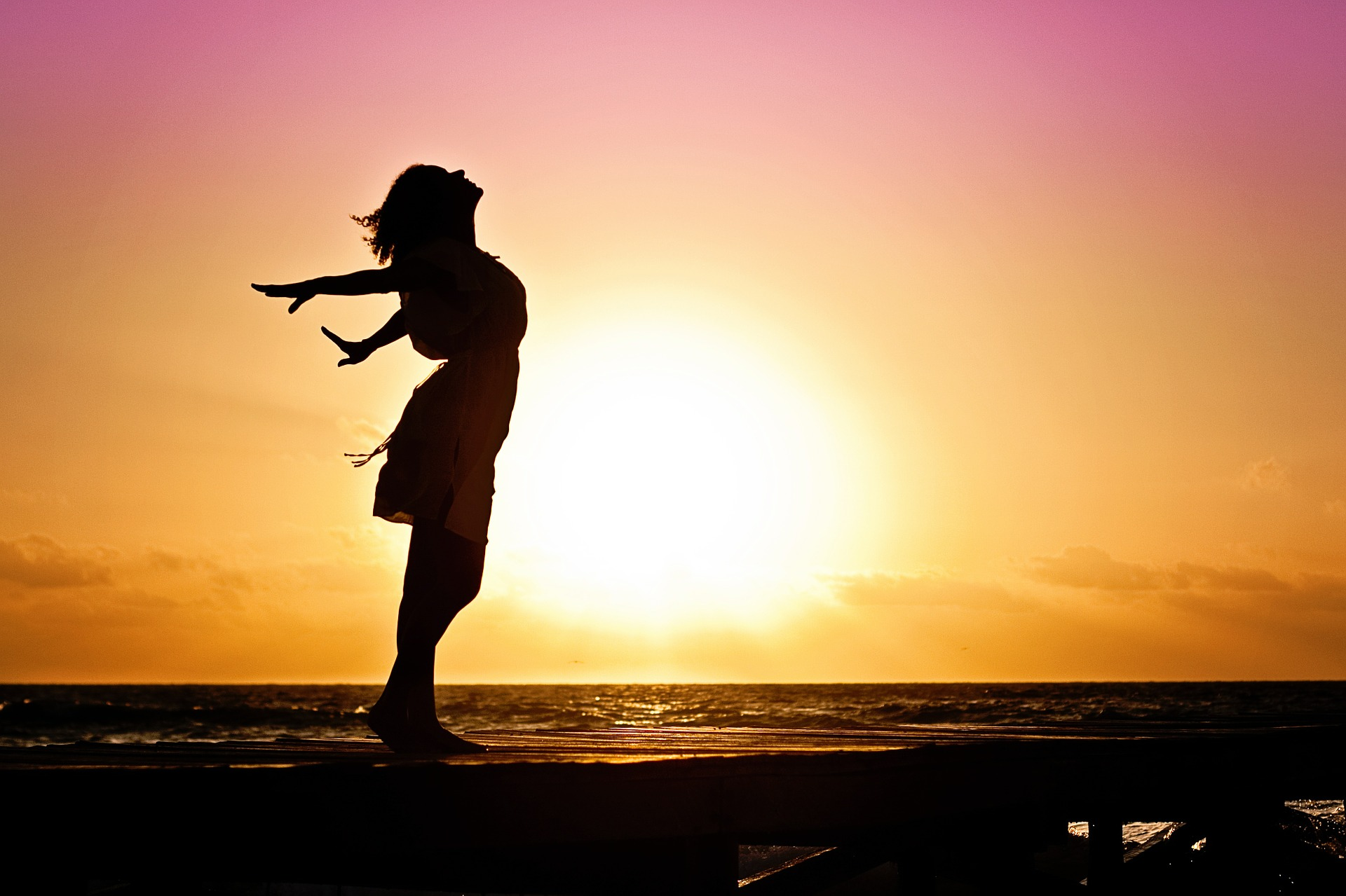 woman at sunset putting her hands back