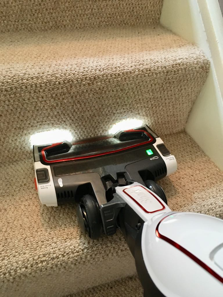 the shark with it's headlights on hoovering the stairs