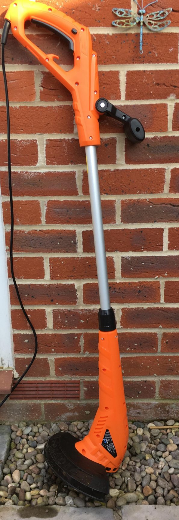 strimmer leaning against a wall