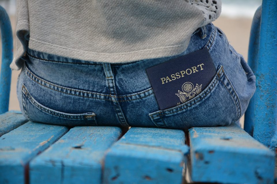 person sat in blue bench with a passport in their back pocket