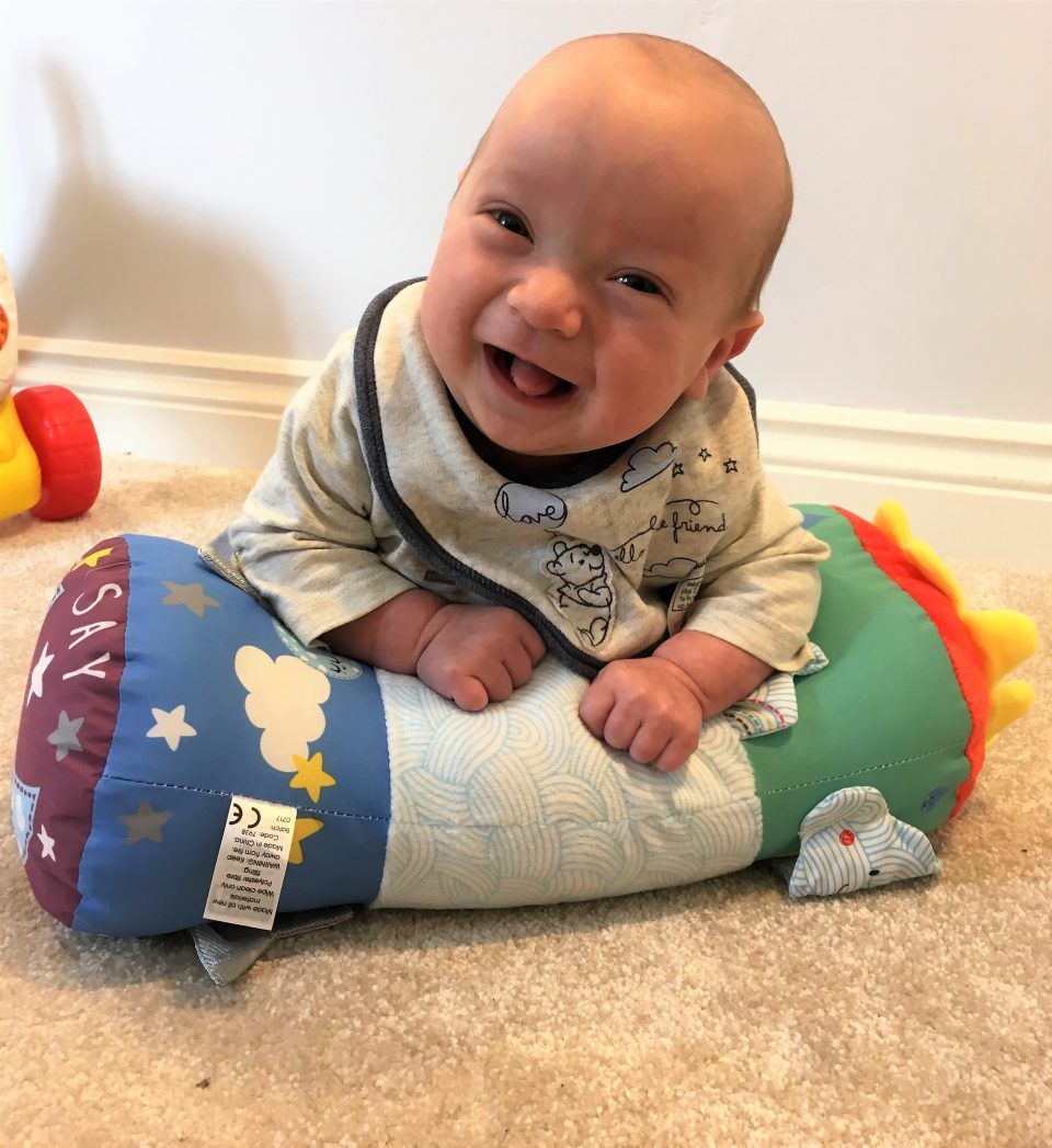 William on his tummytime cushion looking very happy with himself