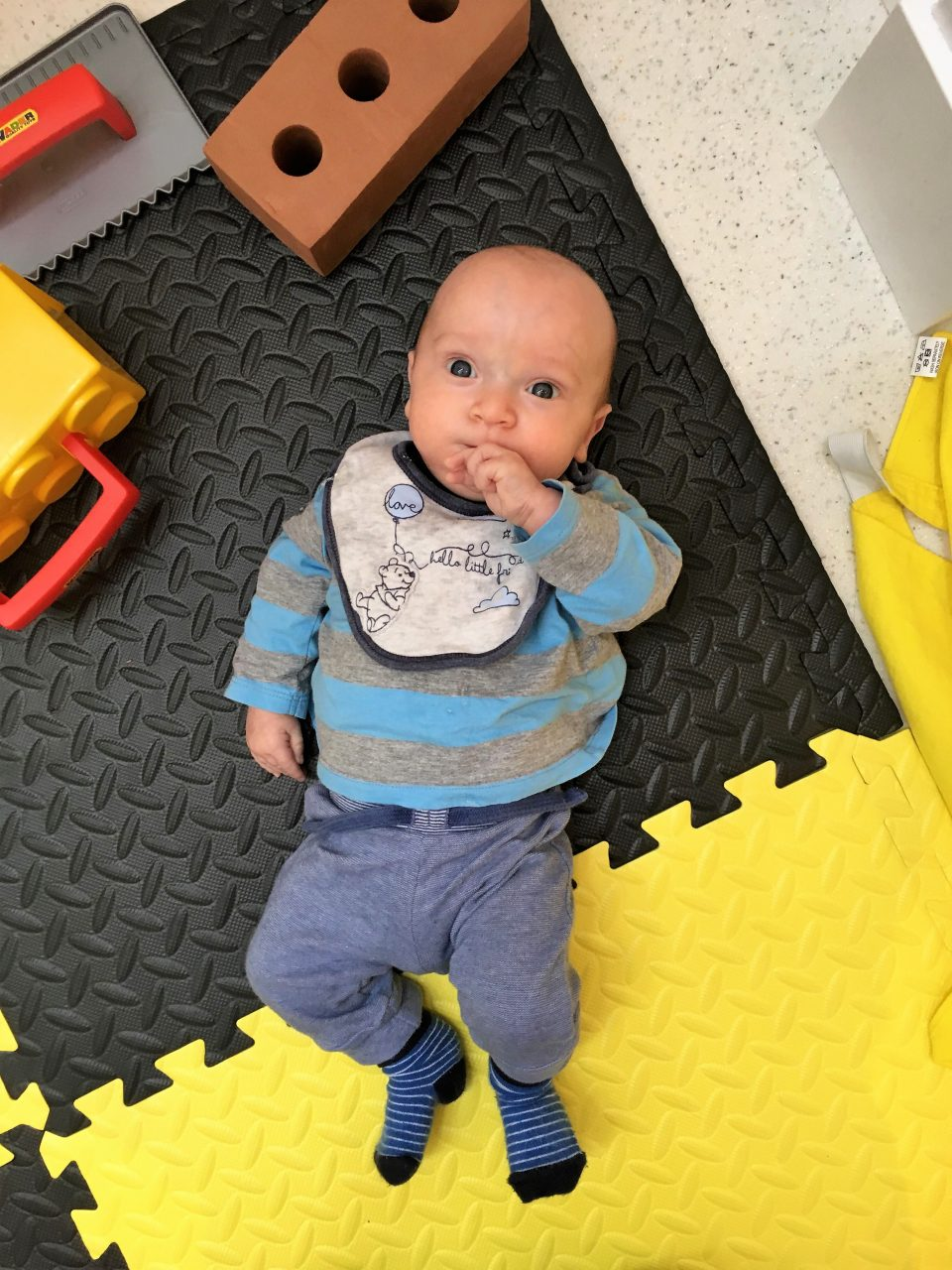 William laying on the floor in little play town