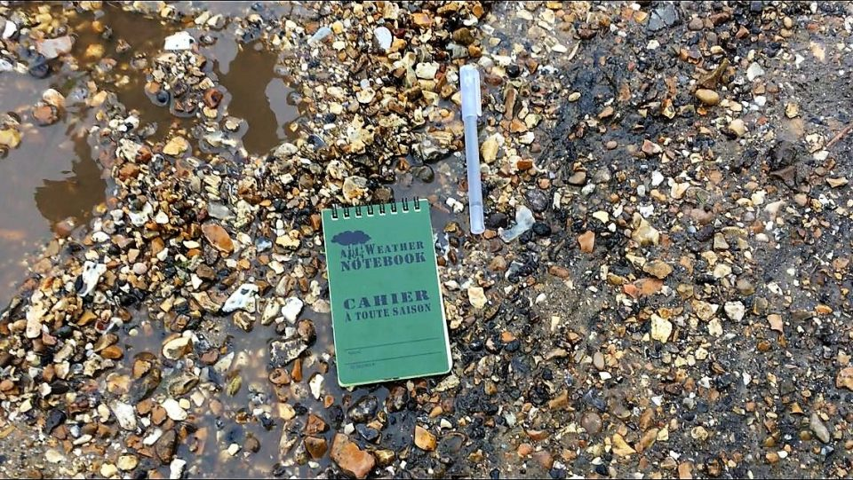 notepad and pen in a puddle on a gravel path