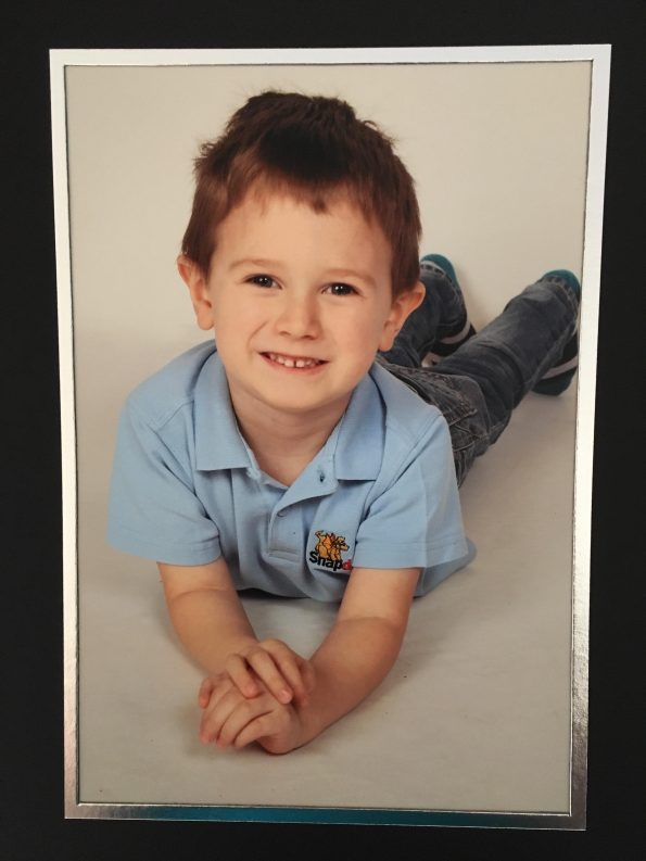 Jake in his pre-school photo laying on the floor