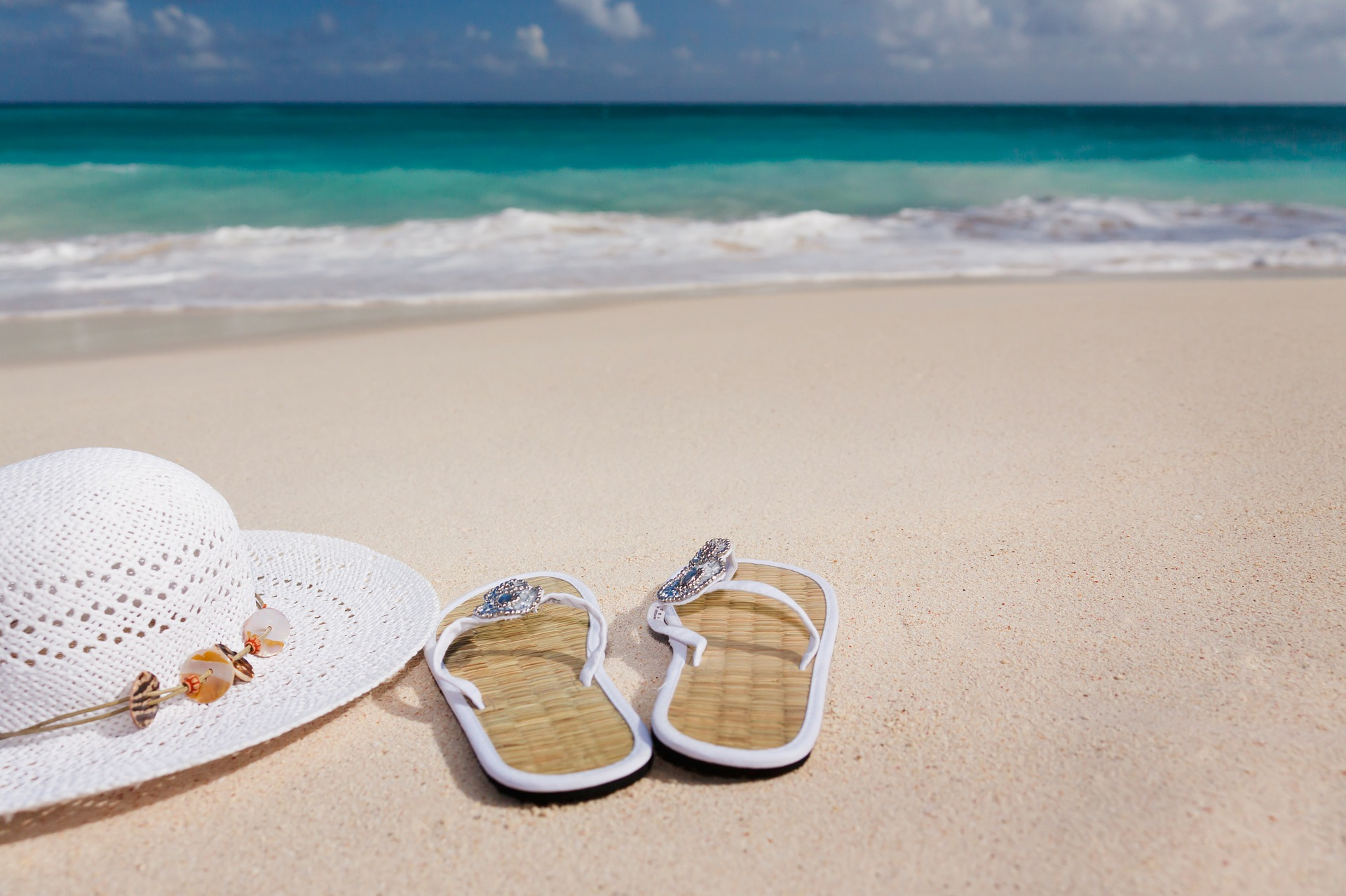 sandals and hat on a beach on a summer holiday