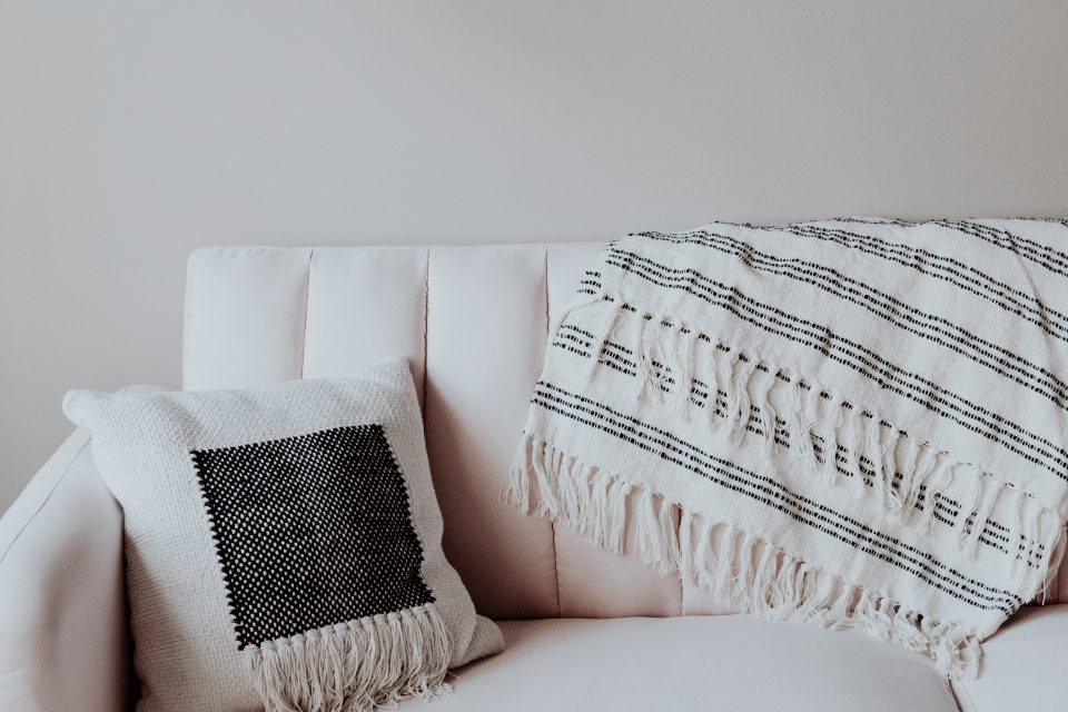 a white sofa with cushion and throw