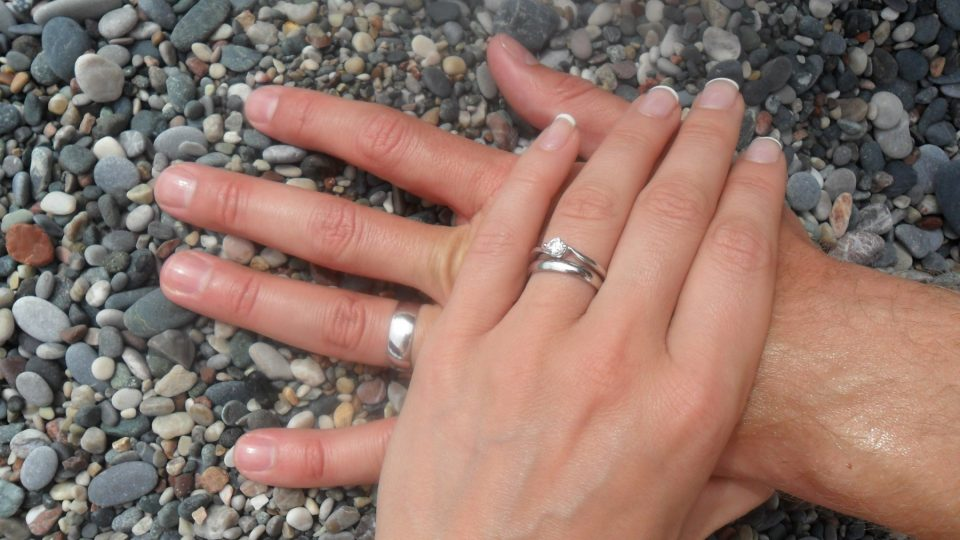 man and woman's hands with wedding rings on