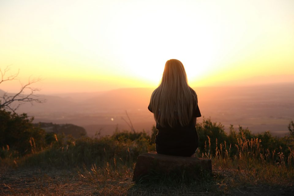 a lady sat on a grass hill looking at a sunset