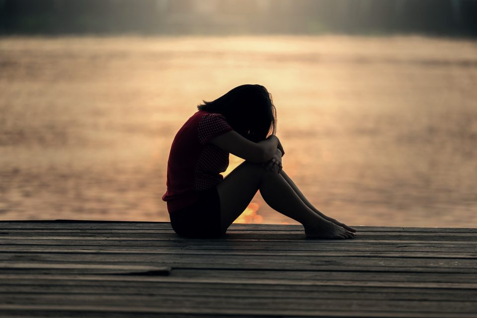 girl sat looking down, sad, depressed