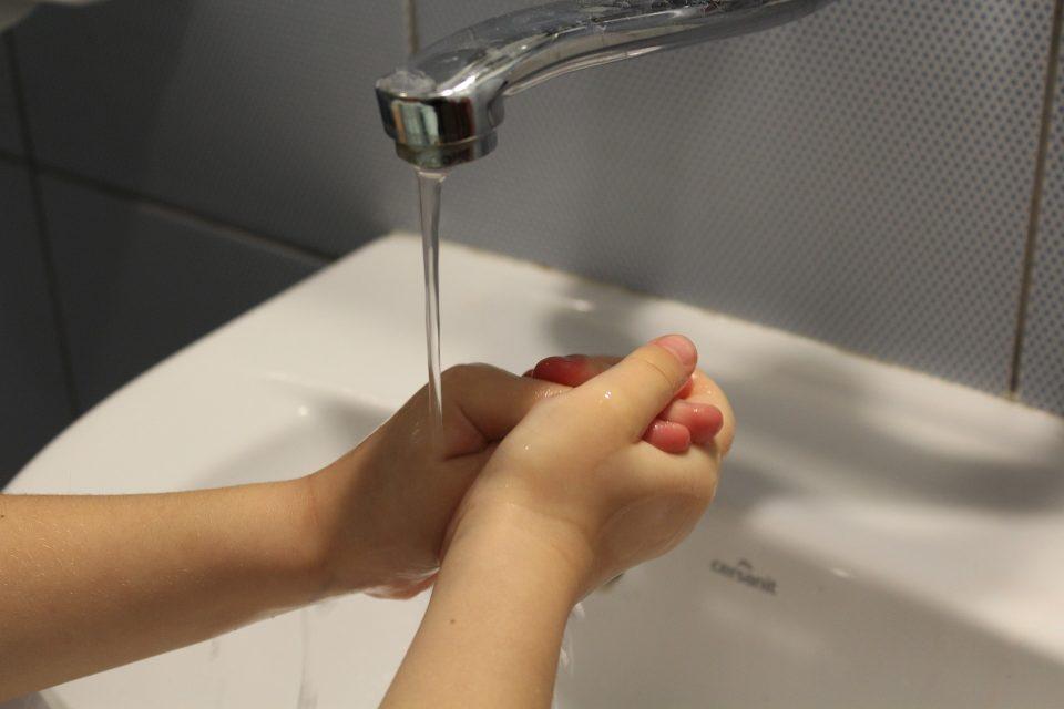 child washing hands under a tap