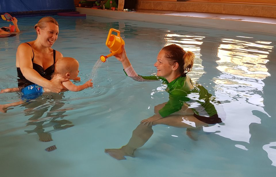 swimming tacher holding a watering can up for baby in pool