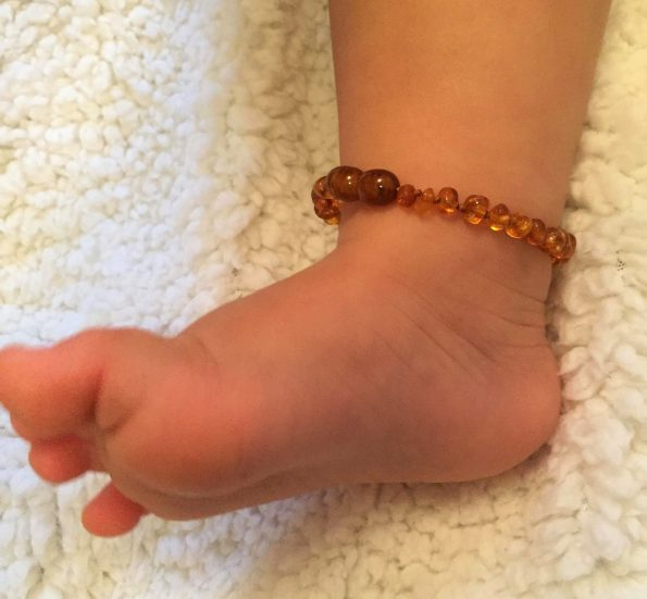 baby's ankle with amber anket