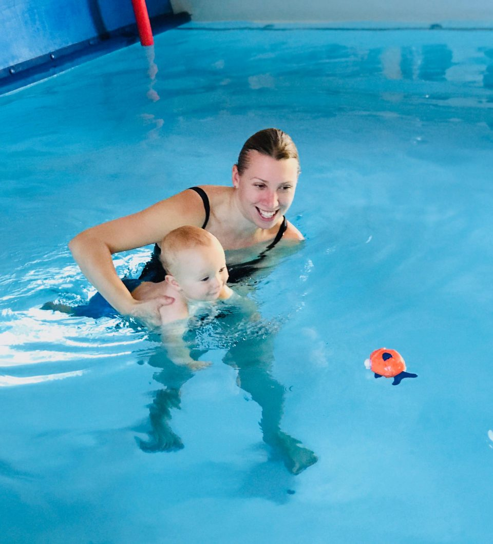 baby in a swim class going for a fish