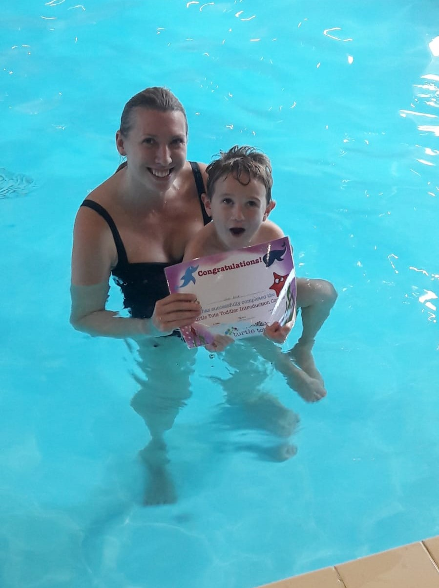 mum and child in pool holding certificate