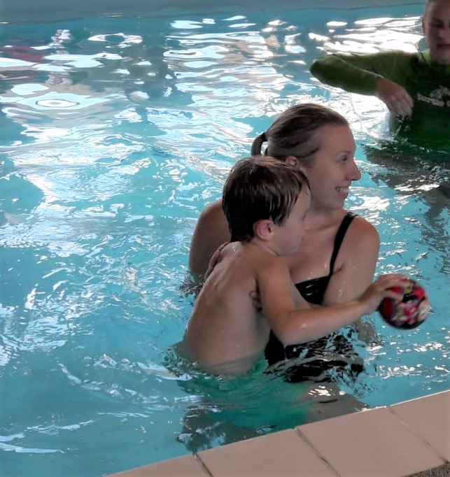 mum and child in pool. Child is holding a ball