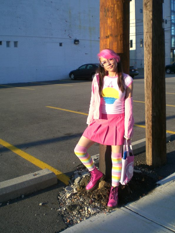 a lady stood next to a wooden pole wearing a lot of pink