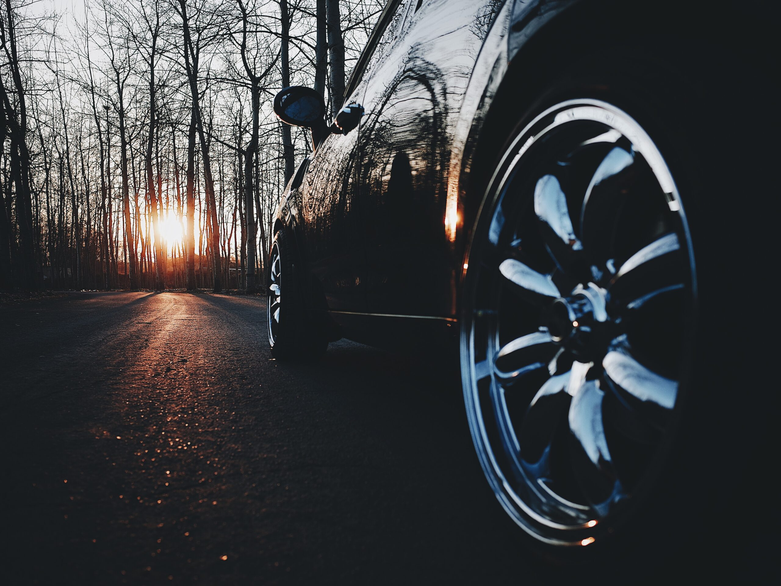 black car on a road at sunset aimed at the tyres thinking about car expenses and maintenance