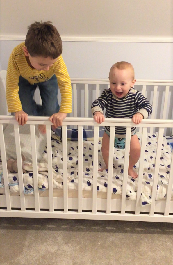 Jake and William jumping in his cot