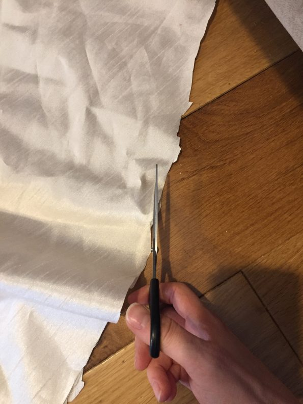 me cutting the curtain with scissors and the edges looking jagged