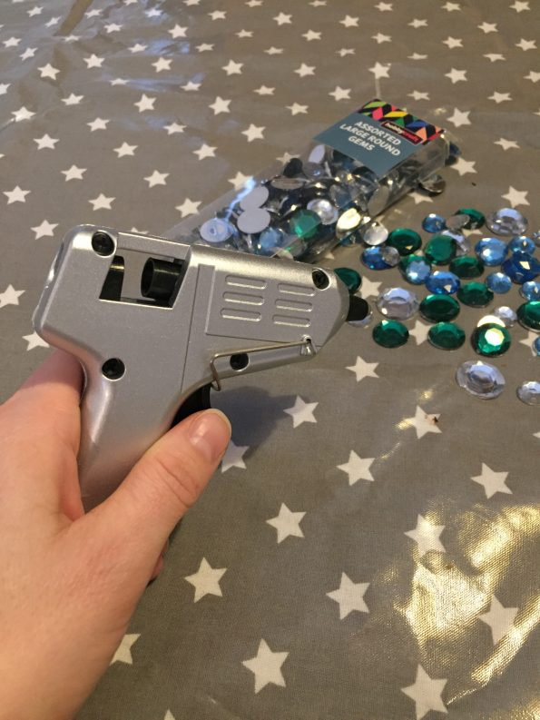 glue gun being held with gems on the table behind