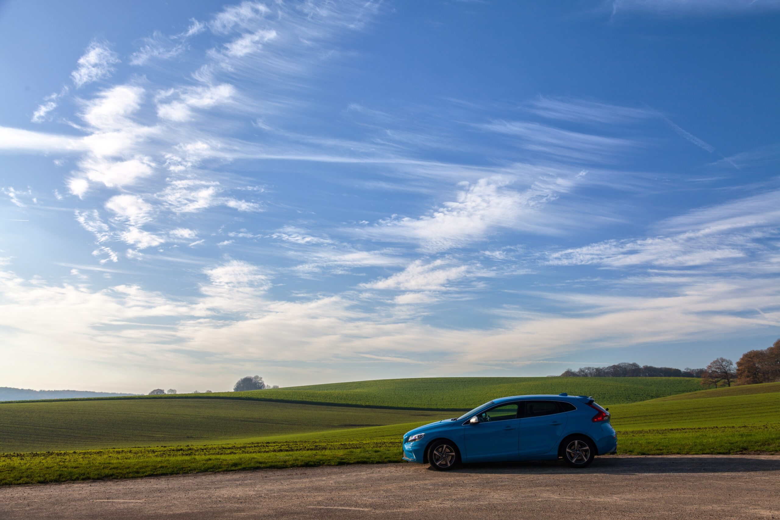 car on a road with a beautiful blue sky