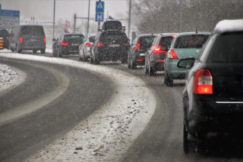 cars driving in cold weather with snow falling