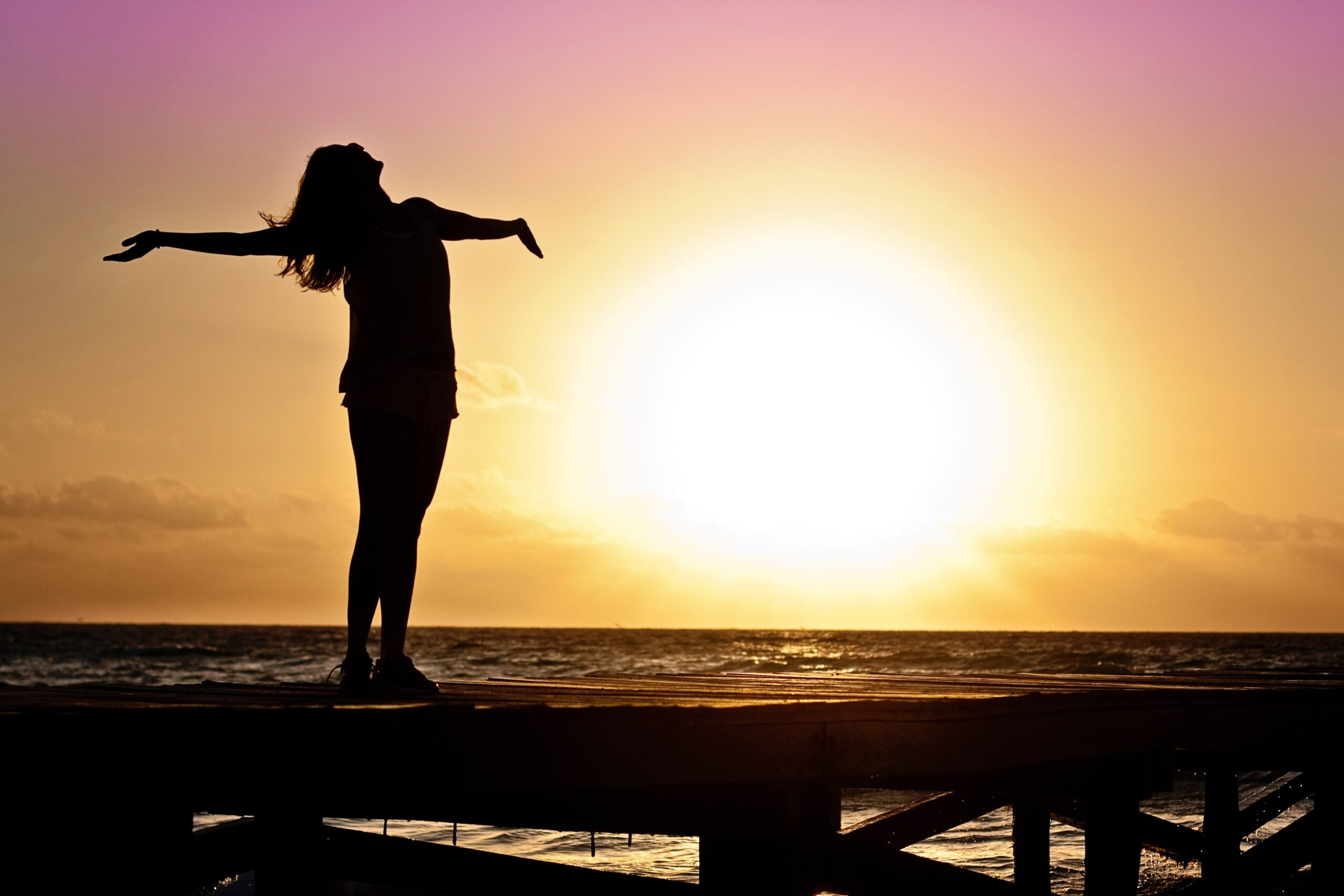 woman leaning back with her arms open on the beach at sunset