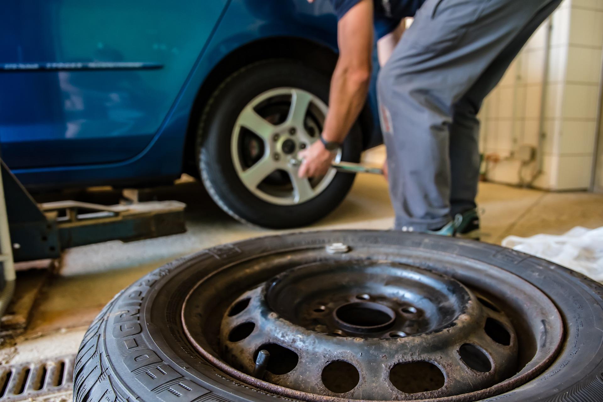 man changing tyre on car