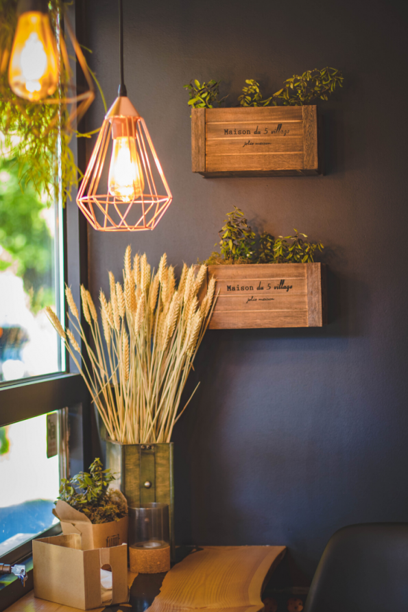 blue wall with crates as flower pots a stunning copper light and wheat in a vase