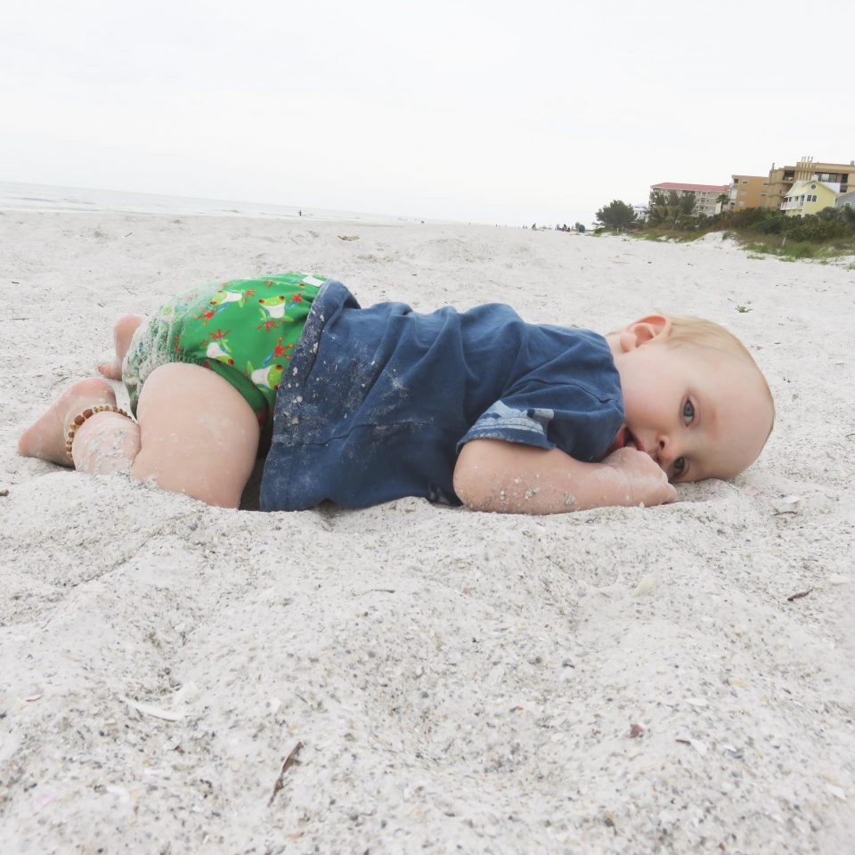 William laying on the beach in his cloth nappy