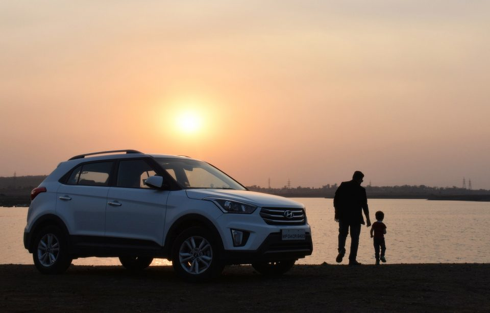 family car at sunset with a dad and child stood next to it