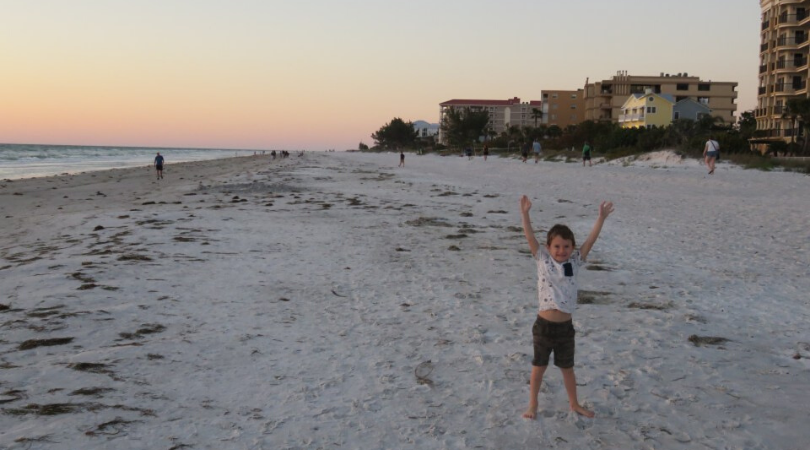 child on a beach with his arms up in the air