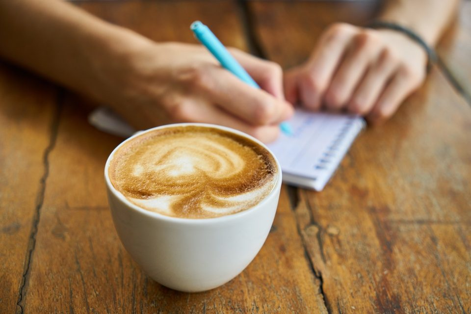 cup of coffee and someone writing a list
