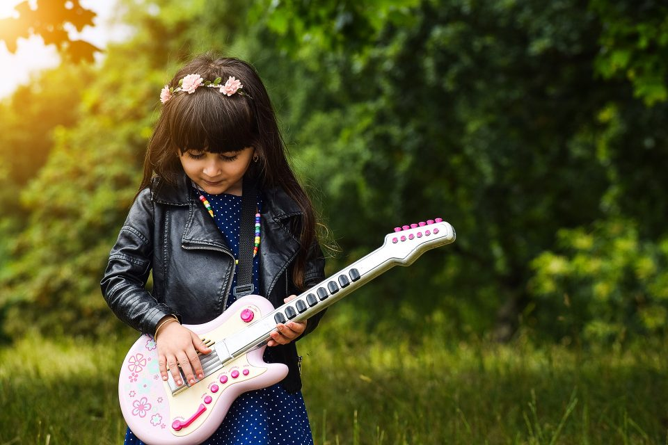 girl playing a guitar outside