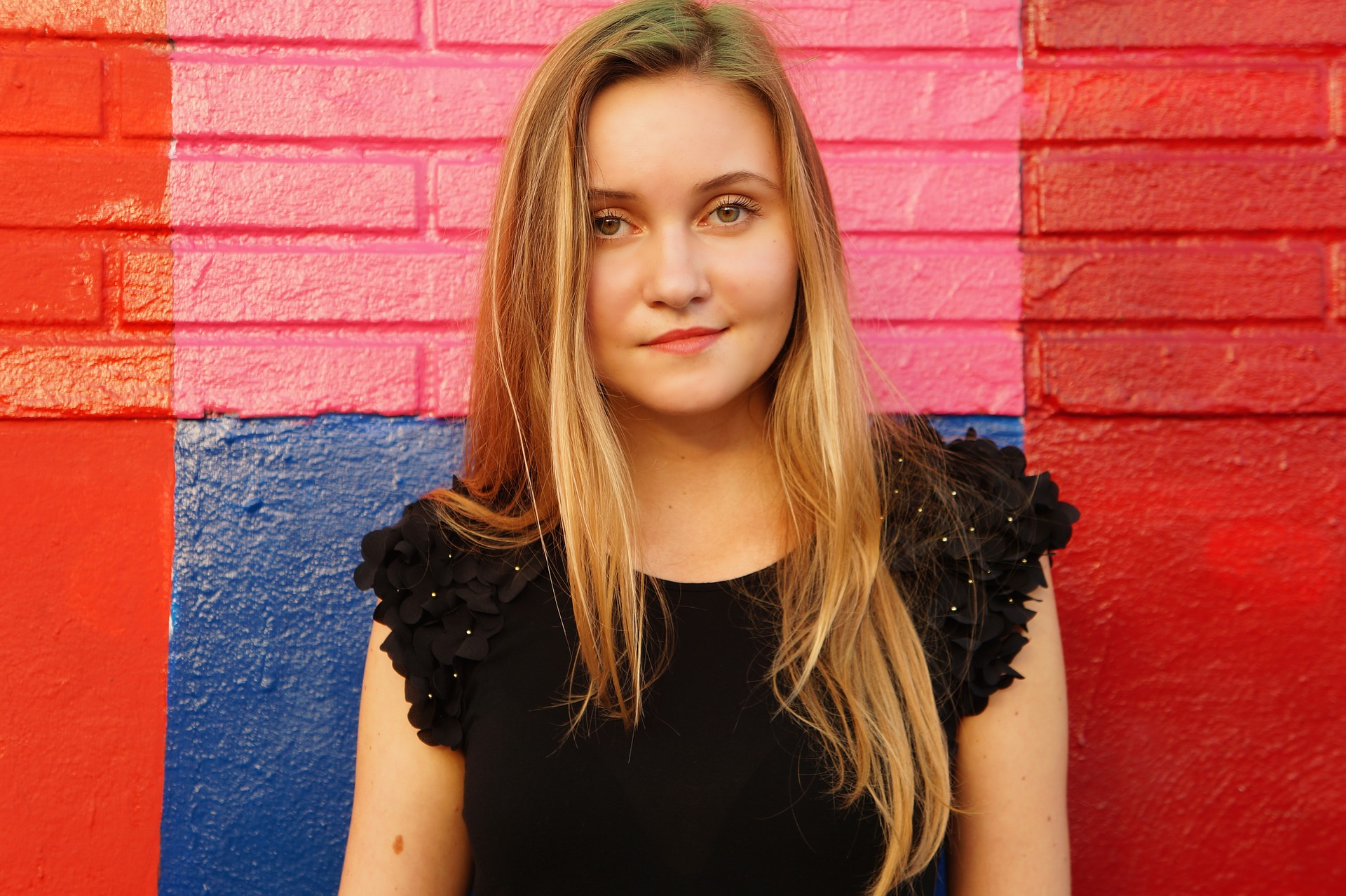 teen girl standing in front of a coloured wall