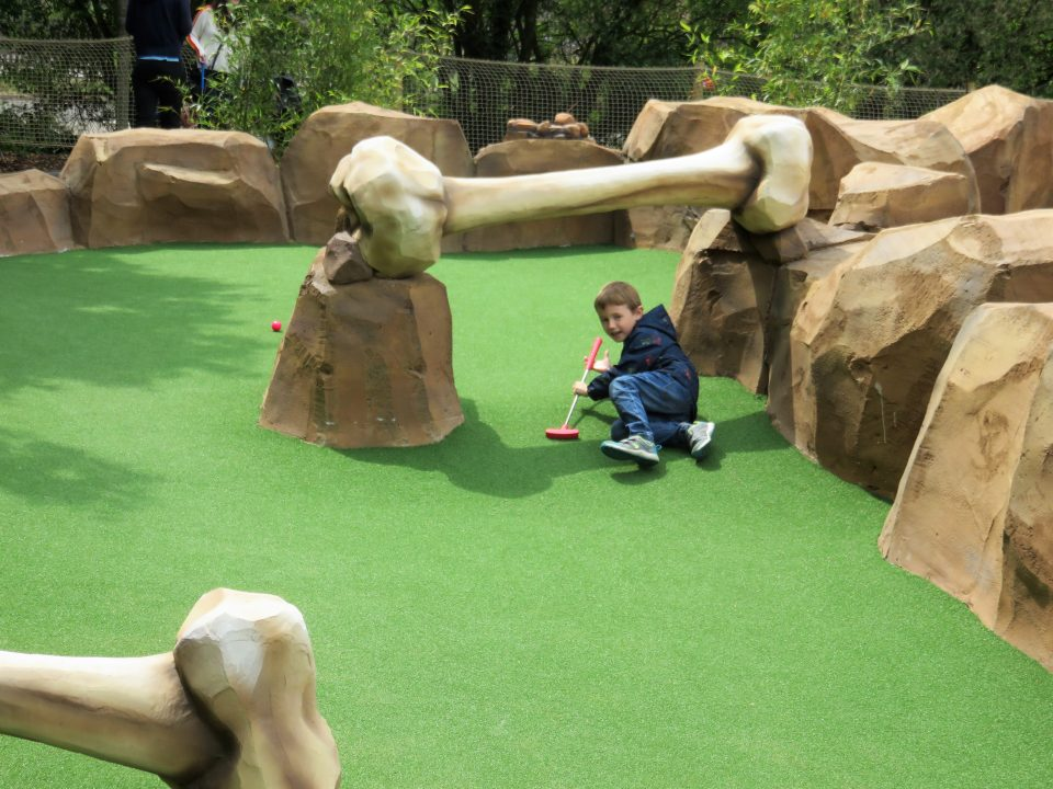 Jake laying on the floor under a big dinosaur bone at mighty claws adventure golf