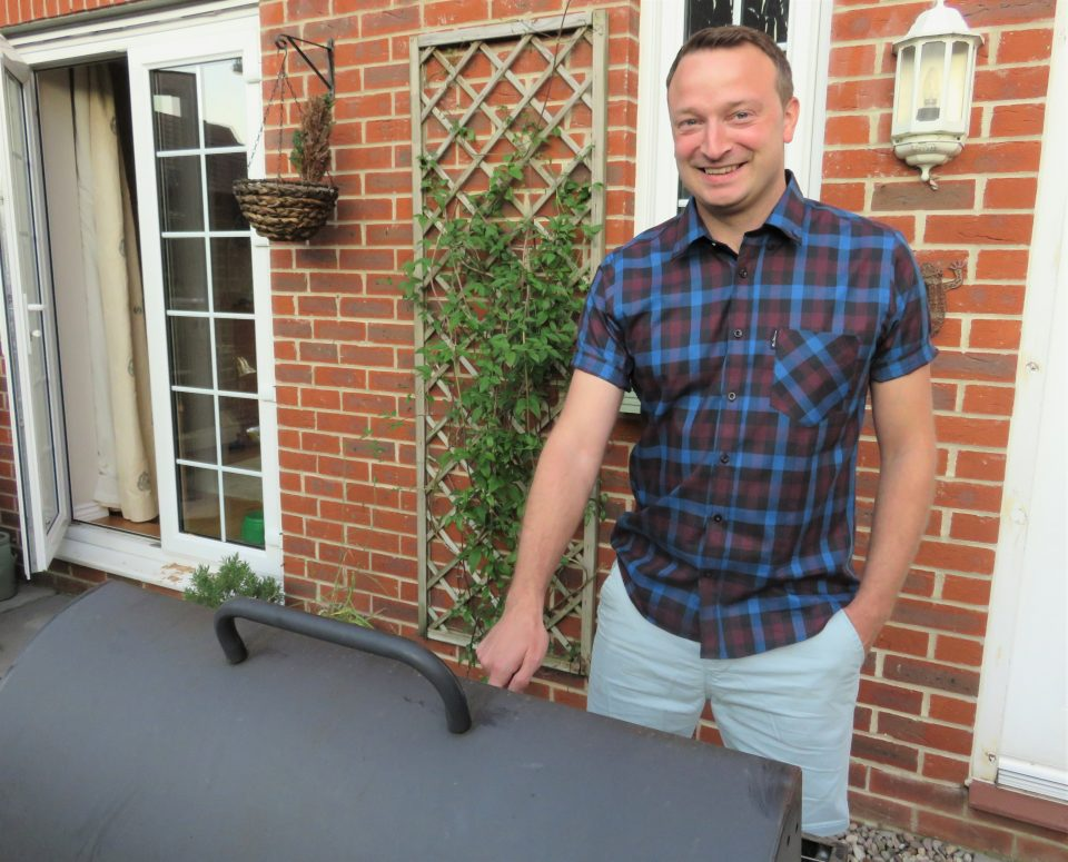 Rob smiling at the camera in his Ben Sherman shirt using the barbeque